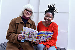 Two women sitting together holding a 2018 Dodge Poetry Festival program
